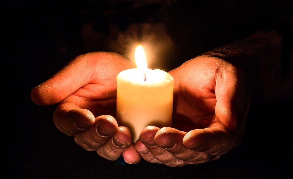 ihminen pitää käsissään kynttilää