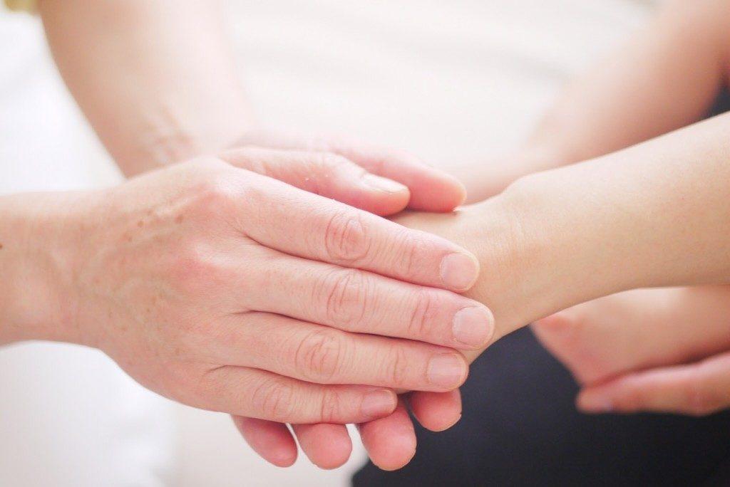 henkilö pitää käsiensä välissä toisen henkilön kättä